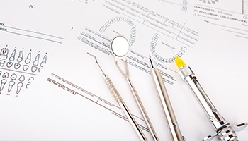 dental tools sitting on dental documents